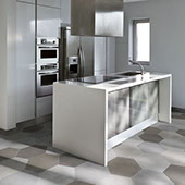 Gray and white kitchen with white cabinetry, stainless appliances, and gray and white twenty inch hexagon porcelain tiles on the floor.