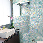 Bathroom with varigated blue glass one by one inch mosaic on the walls and shower. Dark wood vanity with white sink in the foreground.