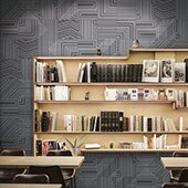 Metallic-look, geometric pattern tile on a library wall.Light wood bookshelves with books and arm chair in the foreground.