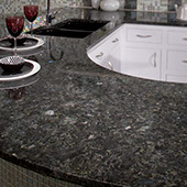 Kitchen peninsula with black, gray, and blue grained granite. Wine glasses on top of the counter.