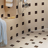 Close up of large shower with bench. Floor, bench, and walls covered with two by two inch ceramic tiles in cream with intermittent squares of maroon tiles.
