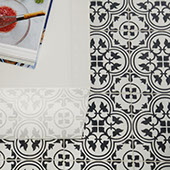 Bird's eye view of a kitchen with black and white intricately patterned encaustic-look tile on the floor with a white waterfall quartz countertop. Open cookbook on the countertop.