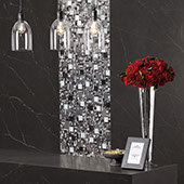 Receiving area with black waterfall quartz slab desk, red flowers in a vase sitting on top. Pendant lighting overhead. Black quartz slab on the walls in the background with vertical stripe of eye-catching glass mosaic.