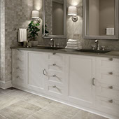 Bathroom double vanity with white cabinetry, framed mirrors, nickel hardware, and white shaded sconces. Warm grey stone-look twelve by twenty four tile on the floor.