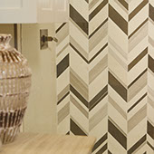 Limestone chevron mosaic feature wall in grey tones with small end table and glass lamp.