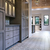 Butler's pantry with dark grey, glass-front cabinetry and grey and white encaustic floor tile.