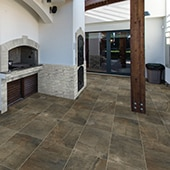 Coverd outdoor patio with outdoor ovens. Sliding glass door visible in the background. Patio floor covered in mottled brown large-format porcelain tile.