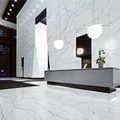 Commercial reception area with tall ceilings. Walls and floor are covered in extra large-format porcelain slab in a classic white marble look.