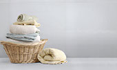 Wicker laundry basket with folded towels and white ceramic tile wall and floor in the background.