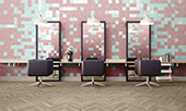 Hair salon with wood-look tile in a herringbone pattern on the floor and wall tiled with four by four inch multi-colored tiles in mint and pink.