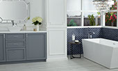 Large bathroom with large windows, soaker tub, grey vanity, with blue fish scale mosaic tile on the wall.