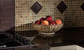 Close up in kitchen with cooktop visible in the bottom right corner. Smooth, dark granite countertops with bowl of fruit. Backsplash with tan mosaic and bronze metallic accents.