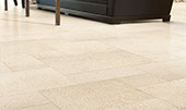 Limestone tile floor in classic creamy limestone beige. Furniture visible in the background.
