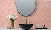 Bathroom vanity with pink fish scale tile on the backsplash with black sink and oval mirror.