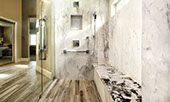 Extra-large shower with bench. Wood-look tile on the floor and marble-look tile on the shower walls.